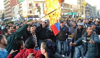 Lebanese anti-Syrian regime protesters burn a Russian flag during a demonstration to show their solidarity with the Syrian people in the northern city of Tripoli, Lebanon, on Saturday, Feb. 4, 2012. (AP Photo)