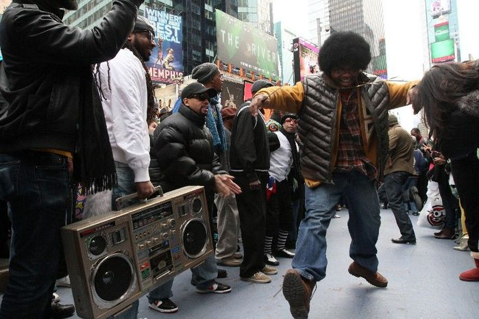 """Participants of a """"Soul Train"""" flash mob make their way along the dance line during a tribute to show creator Don Cornelius Saturday Feb. 4, 2012 in New York's Times Square. (AP Photo/Tina Fineberg)"""