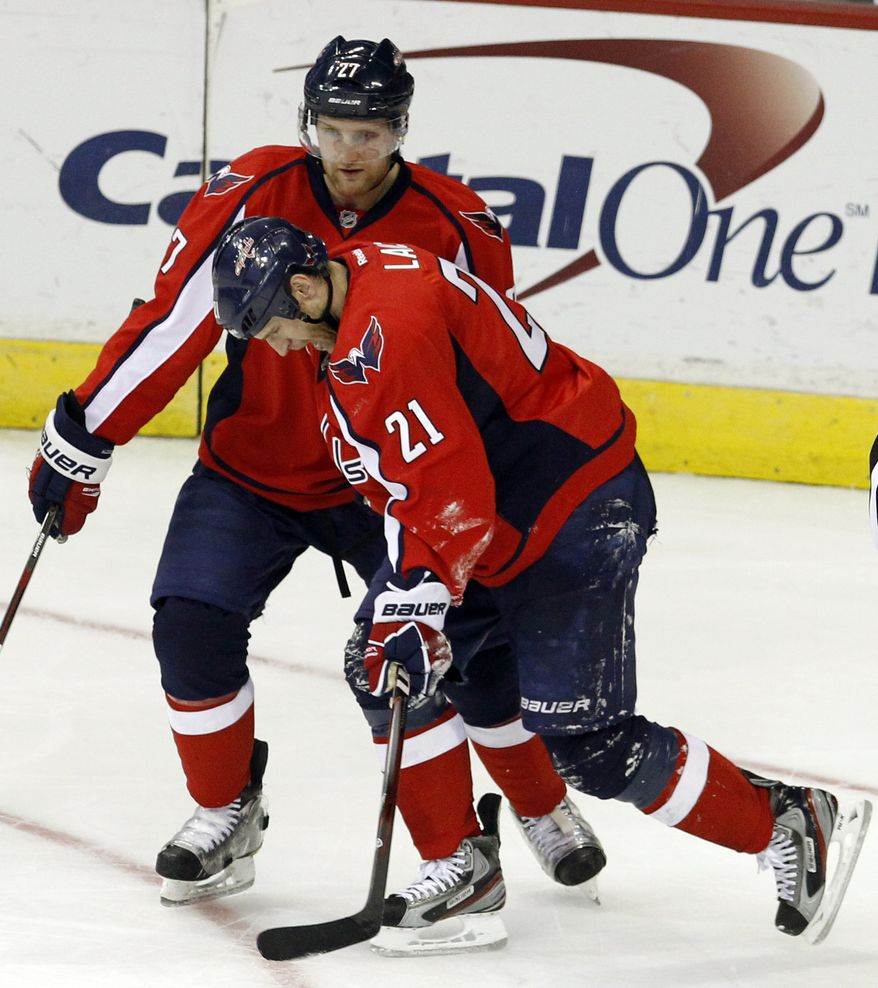 Washington Capitals defenseman Karl Alzner (27) helps injured teammate Brooks Laich (21) off the ice during the second period of an NHL game against the Boston Bruins in Washington, Sunday, Feb. 5, 2012. (AP Photo/Ann Heisenfelt)