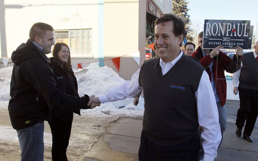Republican presidential candidate former Pennsylvania Sen. Rick Santorum, shakes hands, as a Ron Paul supporter, right, carries a campaign sign behind Santorum, during a campaign stop at the Bemidji, Minn., Woolen Mills store, the manufacturer of the official Santorum for president sweater vest. Sunday, Feb. 5, 2012. (AP Photo/Charles Rex Arbogast)