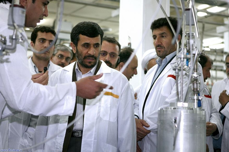 **FILE** Iranian President Mahmoud Ahmadinejad (center) listens April 8, 2008, to a technician during his visit of the Natanz Uranium Enrichment Facility, located about 200 miles (322 kilometers) south of Tehran. (Associated Press/Iranian President's office)
