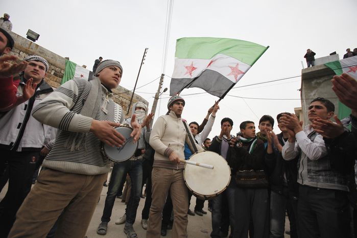 Anti-Syrian regime protesters play drums and wave a revolutionary flag Feb. 6, 2012, during a demonstration in Idlib, Syria. (Associated Press)