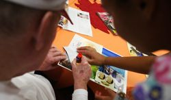 **FILE** Monica Leon Galarza (right), a nursing assistant, helps Archie, a resident, make a collage on Oct. 15, 2009, during an art program at the Alzheimer's disease unit of the Patriots Colony retirement community in Williamsburg, Va. (Associated Press/The Daily Press)