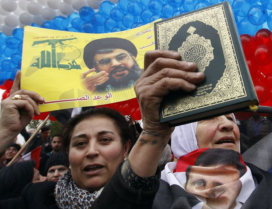"""A pro-Syrian regime protester (left), holding a poster of Hezbollah leader Sheik Hassan Nasrallah with Arabic that reads """"Hezbollah"""", cheers a convoy believed to be transporting Russian Foreign Minister Sergey Lavrov in Damascus, Syria, on Feb. 7, 2012. (Associated Press)"""