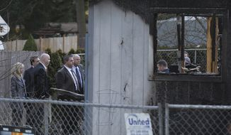 Police and other officials from Washington state and Utah view charred rubble on Feb. 6, 2012, at the home where Josh Powell and his two sons were killed two days earlier in Graham, Wash., in what police said appeared to be a deliberately set fire. Powell's wife Susan went mysteriously missing from their West Valley City, Utah, home in December 2009. (Associated Press)