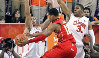 Maryland's Terrell Stoglin (12) drives the lane between Clemson's Milton Jennings, left, and Devin Booker in the second half of an NCAA college basketball game against Clemson on Tuesday, Feb. 7, 2012 in Clemson, S.C. (AP Photo/Anderson Independent-Mail, Mark Crammer) GREENVILLE NEWS, SENECA JOURNAL - OUT