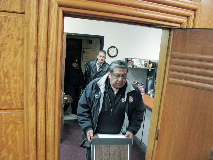 Archie Fool Bear, of Fort Yates, N.D., a former Standing Rock Sioux tribal council member, carries a box of petitions into the North Dakota Secretary of State's Office in Bismarck, N.D., on Tuesday. The petitions call for a vote on keeping the state university's Fighting Sioux nickname and logo. (Associated Press)