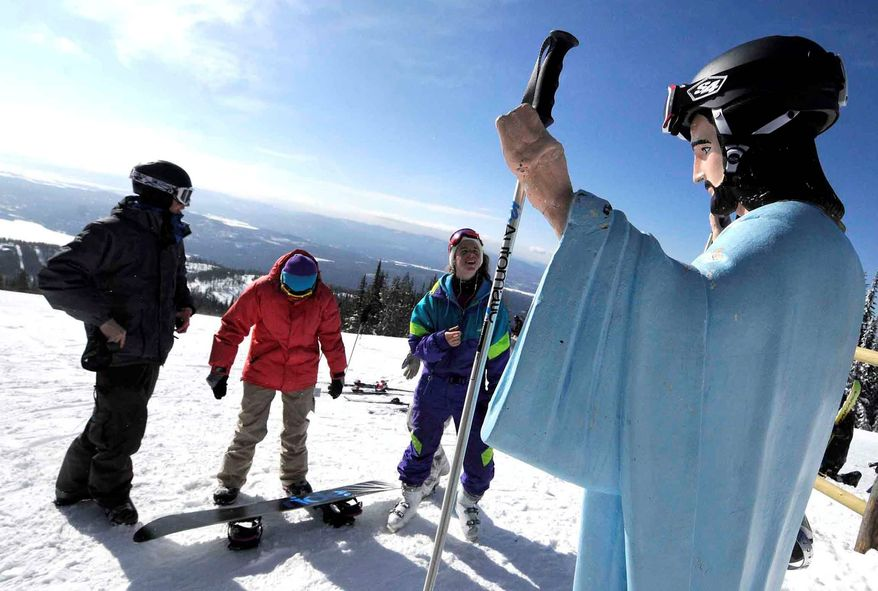 ** FILE ** This Feb. 20, 2011, file photo shows freshman at the University of Montana, from left, Jake Coburn, Stephanie Ralls and Claire Dal Nogare, visiting a statue of Jesus Christ at Whitefish Mountain Resort Sunday, Feb. 20, 2011, in Whitefish, Mont. An atheist group has filed a lawsuit demanding the removal of this mountaintop Jesus statue on federal land in northwestern Montana after the U.S. Forest Service reversed itself amid an outcry and said the statue could stay. (AP Photo/Missoulian, Linda Thompson, File)