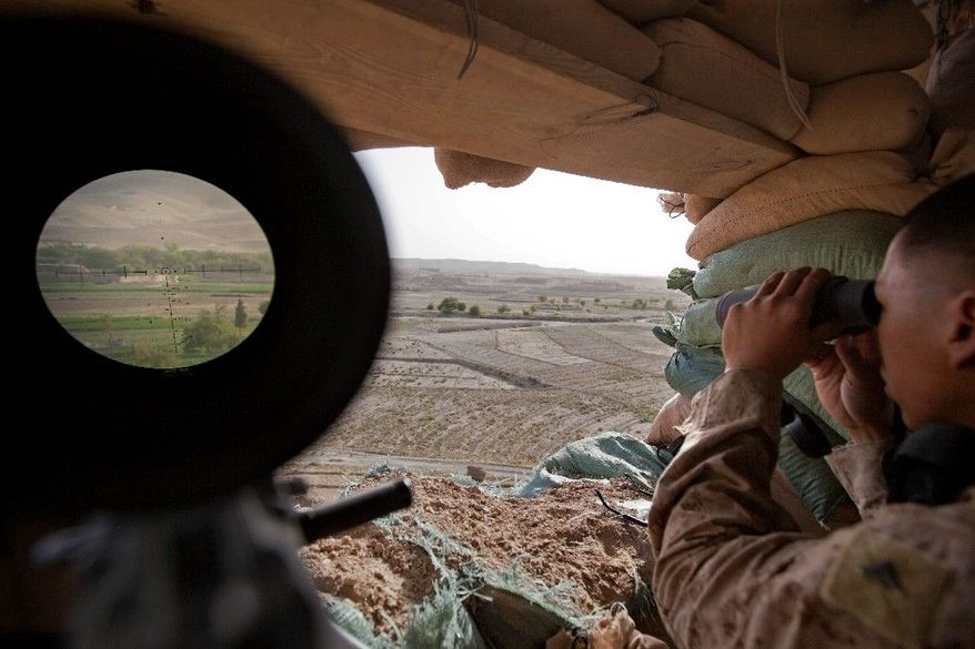 The village of Shabaz Kheyl is seen through a scope at left on a machine gun as U.S. Marine Lance Cpl. Larry Alqueza, 23, of El Paso, Texas, with the 2nd Battalion 12th Marines based in Kaneohe Bay, Hawaii, looks through binoculars for insurgent movement from a mountain top outpost called the Shrine Saturday, July 30, 2011 in Kajaki, Helmand province, Afghanistan. (AP Photo/David Goldman)