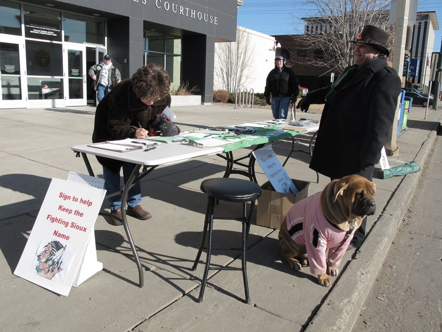 Charles Tuttle, a backer of the University of North Dakota's Fighting Sioux nickname, watches Feb. 7, 2012, as a woman signs petitions supporting the nickname in front of the federal courthouse in Bismarck, N.D. (Associated Press)