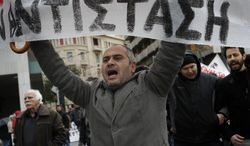 """A Greek protester holds a banner with the word """"resistance'' during a 24-hour strike in Athens on Tuesday, Feb. 7, 2012. (AP Photo/Petros Giannakouris)"""