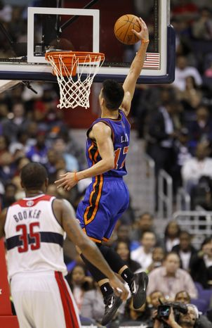 New York Knicks point guard Jeremy Lin (17) goes up for a dunk in front of Washington Wizards forward Trevor Booker (35) during the second half of an NBA game, Wednesday, Feb. 8, 2012, in Washington. The Knicks won 107-93. (AP Photo/Haraz N. Ghanbari)