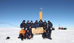 """Russian researchers at the Vostok station in Antarctica pose for a picture Feb. 5, 2012, after reaching subglacial lake Vostok, a major scientific discovery that could provide clues for search for life on other planets. Scientists hold a sign reading """"05.02.12, Vostok station, boreshaft 5gr, lake at depth 3769.3 metres."""" (Associated Press/Arctic and Antarctic Research Institute Press Service)"""