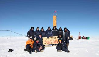 "Russian researchers at the Vostok station in Antarctica pose for a picture Feb. 5, 2012, after reaching subglacial lake Vostok, a major scientific discovery that could provide clues for search for life on other planets. Scientists hold a sign reading ""05.02.12, Vostok station, boreshaft 5gr, lake at depth 3769.3 metres."" (Associated Press/Arctic and Antarctic Research Institute Press Service)"
