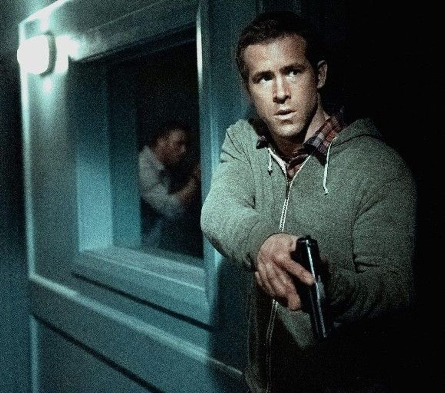 """Ryan Reynolds is a CIA agent who has to flee a safe house with a prisoner in tow in """"Safe House."""" (Universal Pictures via Associated Press)"""