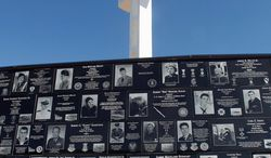 Plaques honoring war veterans surround a cross at the Mount Soledad Memorial in San Diego. They honor an estimated 3,000 service people. But the 43-foot-high monument, which sits on federal land, has been deemed to be in violation of the Constitution's separation of church and state. Supporters are seeking a ruling reversal in court. (Associated Press)