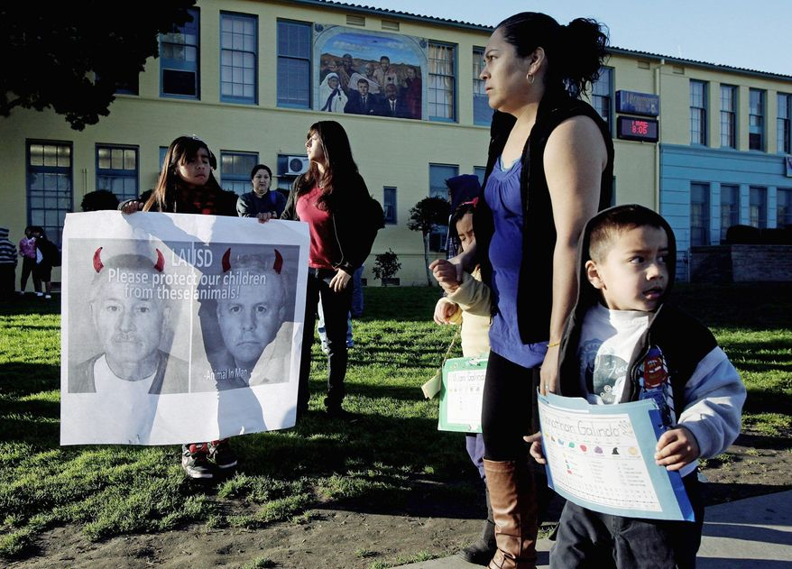 Ashley Villatoro (left) holds a poster showing former teacher Martin B. Springer as students arrive at Miramonte Elementary School in Los Angeles on Thursday. Children return to the school where the entire staff has been replaced. (Associated Press)