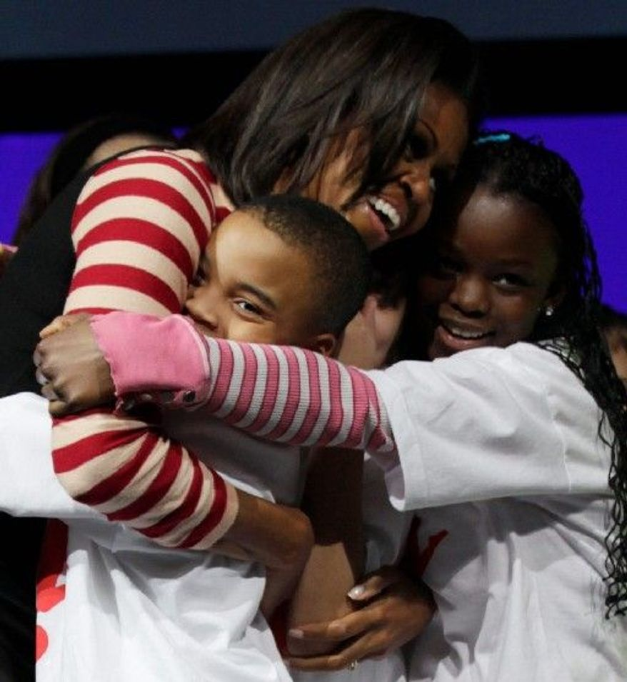 "First lady Michelle Obama hugs her dance partners after doing the Interlude dance during a ""Let's Move"" pep rally supporting healthy eating and exercise Thursday with schoolchildren in Des Moines, Iowa. (Associated Press)"
