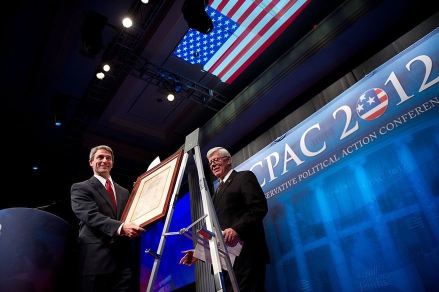 """Virginia Attorney General Ken Cuccinelli, left, accepts the """"Defender of the Constitution Award"""" from National Rifle Association President David Keene, center, at the Conservative Political Action Conference (CPAC) held at the Marriott Wardman Park, Washington, DC, Thursday, February 9, 2012. The annual political conference draws thousands of supporters and prominent conservative figures. (Andrew Harnik / The Washington Times)"""