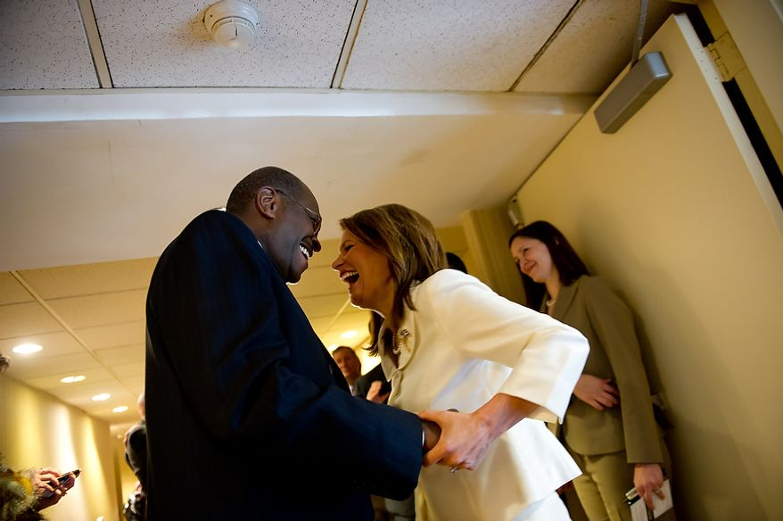 Former Republican presidential candidates Michele Bachmann and Herman Cain share a laugh after running into each other backstage at the Conservative Political Action Conference (CPAC) on Feb. 9, 2012, at the Marriott Wardman Park in D.C. The annual political conference draws thousands of supporters and prominent conservative figures. (Andrew Harnik/The Washington Times)