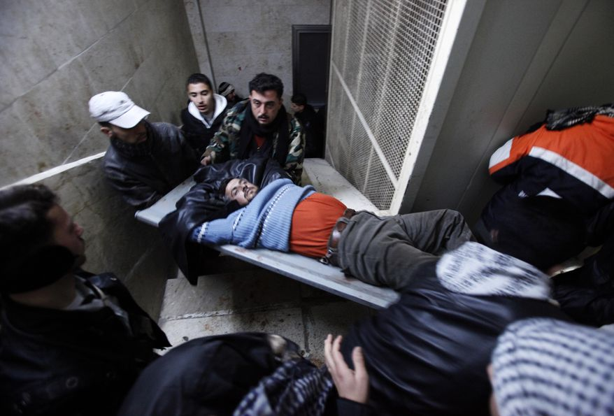 An injured Syrian rebel fighter is carried into a hospital following an exchange of fire with government troops in Idlib, Syria, on Wednesday, Feb. 8, 2012.  (AP Photo)