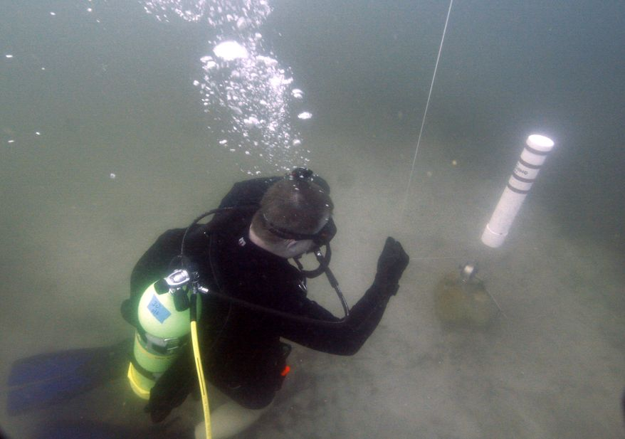 In this Saturday, Jan. 14, 2012 photo, Kenny Jenkins places a weight and geocache marker in about 33 ft. of water in Lake Denton in Avon Park, Fla. Interest in geocaching has grown significantly over the years. But combining the two hobbies, geocaching and scuba diving, has only recently taken off. About 100 geocaches around the world today are only accessible with scuba gear, according to the geocaching.com database. (AP Photo/Wilfredo Lee)