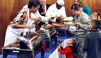 **FILE** First lady Michelle Obama (left) serves food to U.S. airmen and their relatives at Ramstein Airbase in Ramstein, Germany, on Nov. 11, 2010. (Associated Press)