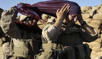 ** FILE ** U.S. Marine Sgt. Monica Perez (left) of San Diego helps Lance Cpl. Mary Shloss of Hammond, Ind., put on her head scarf before heading out on a patrol in the village of Khwaja Jamal in the Helmand province of Afghanistan in August 2009. (AP Photo/Julie Jacobson, File)
