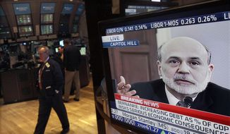 Federal Reserve Chairman Ben Bernanke's testimony before the House Budget Committee on Feb. 2, 2012, is visible on a television screen on the floor of the New York Stock Exchange. (Associated Press)