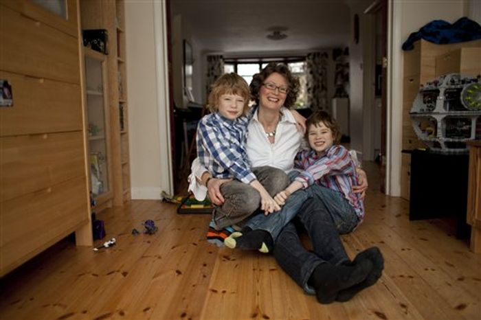 In this Thursday, Feb. 9, 2012 photo, Caroline Swain poses for photographs with her sons Max, left, 10, and Luke, 9, at their home in Rayleigh, England. Swain was diagnosed with breast cancer while pregnant with Luke. She had her left breast and many lymph nodes removed and had to wait until her fetus was 12-weeks-old before starting chemotherapy. Researchers have encouraging news for women who have cancer while pregnant. Studies suggest that these women can be treated almost the same as other cancer patients are, with minimal risk to the fetus. (AP Photo/Matt Dunham)