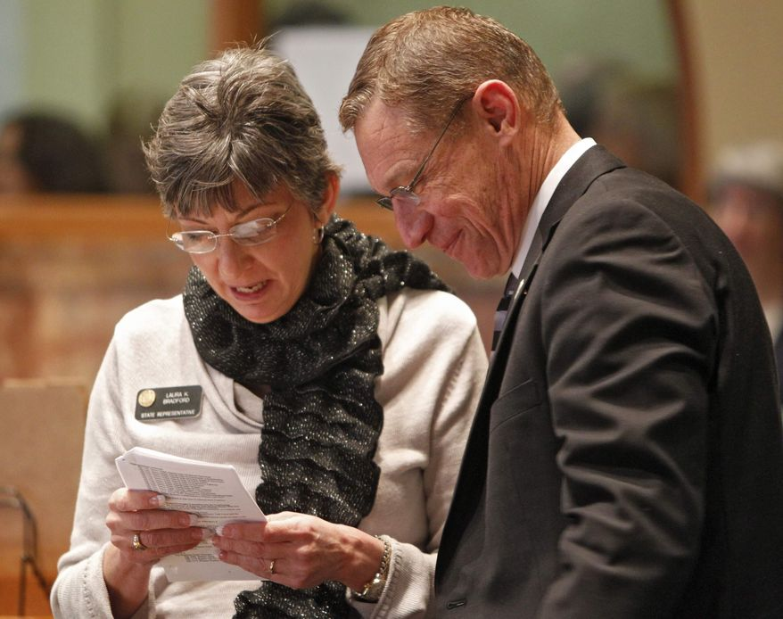 ** FILE ** This photo taken at the Capitol on Thursday, Feb. 2, 2012, shows Rep. Laura Bradford, left, R-Collbran, talking to Rep. Ken Summers, R-Lakewood, in the House chambers. (AP Photo/Ed Andrieski)