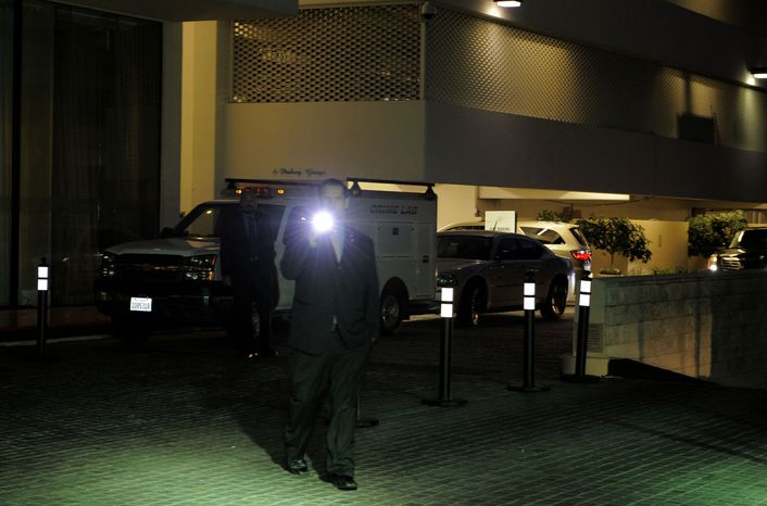 Security gather outside the Beverly Hilton Hotel Saturday Feb. 11, 2012 in Beverly Hills Calif. Whitney Houston, who ruled as pop music's queen until her majestic voice and regal image were ravaged by drug use, erratic behavior and a tumultuous marriage to sin