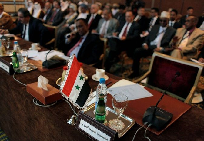 """The Syrian flag and a sign in Arabic that reads """"the Syrian Arabic Republic"""" mark the empty chair of the Syrian representative during the Arab League Syria Group and fo"""