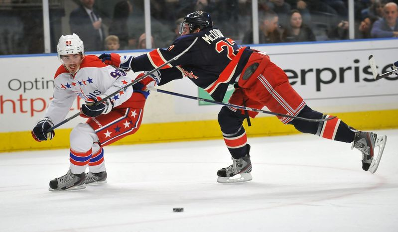 New York Rangers' Ryan McDonagh pushes Washington Capitals' Marcus Johansson off the puck during the first period of an NHL game Sunday, Feb. 12, 2012, in New York. (AP Photo/Newsday, David Pokre