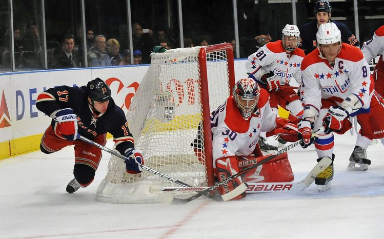 New York Rangers' Brandon Dubinsky, left, tries a wraparound shot in the second period of an NHL game but the shot is blocked by Washington Capitals goalie Michal Neuvirth in New York, Sunday, Feb. 12, 2012. (AP Photo/Newsday, David Pokress)