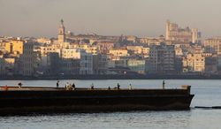 The city of Havana can be seen in the background as people fish from a dock in Havana Bay. The United States imposed an economic embargo on Cuba 50 years ago to pressure the regime of Fidel Castro. (Associated Press)