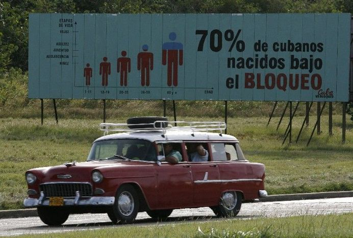 "A car drives past a billboard in Havana in 2006 that reads in Spanish ""70 percent of Cubans have been born under the embargo."" Cuba updates its estimate of how much the embargo has cost it using a complicated - and some say flawed - calculus. (Associated Press)"