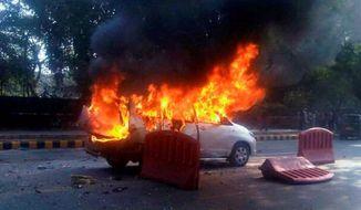 A car belonging to the Israeli Embassy goes up in flames Monday in New Delhi after a magnetic bomb attached to the car exploded, injuring four people. A similar bomb on an Israeli diplomatic car in Georgia was defused. (Economic via Associated Press)