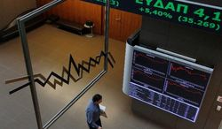 """An employee of the Greek Stock Exchange passes past charts with stock prices, indicating gains, in Athens on Monday. World stock markets rose Monday after Greece's parliament approved a new set of austerity measures that were required by international lenders in exchange for an emergency bailout. The move was labeled a """"crucial step forward."""" (Associated Press)"""