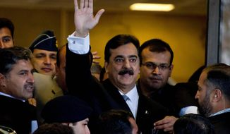 Pakistani Prime Minister Yousuf Raza Gilani arrives at the Supreme Court for a hearing in Islamabad on Monday. Judges charged Mr. Gilani with contempt for defying their orders to reopen an old corruption case against his political ally, President Asif Ali Zardari. (Associated Press)