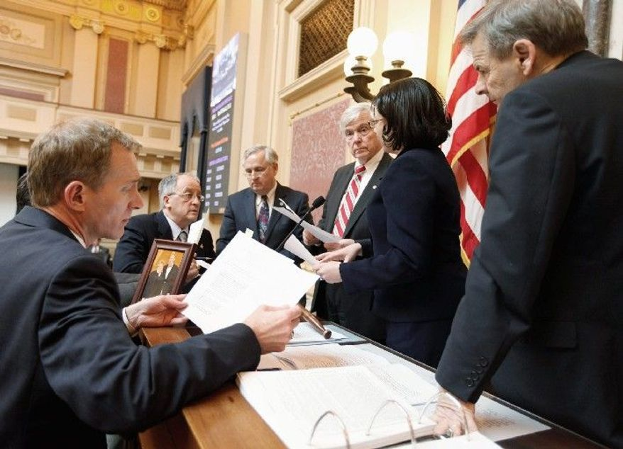 Virginia House clerk G. Paul Nardo (left) listens Monday to Delegate Jennifer L. McClellan (second from right) as she speaks with House Speaker William J. Howell (third from right) at the Capitol in Richmond. The Republican party has enjoyed a banner first half of the General Assembly session, pushing through far-reaching legislation. (Associated Press)