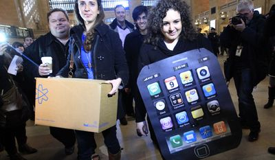 **FILE** Sarah Ryan (left) and Shelby Knox of Change.org arrive Feb. 9, 2012, at the Apple store at Grand Central Terminal in New York to deliver petitions asking Apple to change its manufacturing practices and to address criticism of worker conditions at manufacturing partners operating in China. (Associated Press)