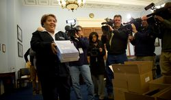 Patricia Gillaird, a Government Printing Office receiving clerk, displays for news crews a copy of the fiscal 2013 budget at the Cannon House Office Building on Capitol Hill in Washington on Monday, Feb. 13, 2012. (Rod Lamkey Jr./The Washington Times)