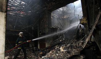 A firefighter extinguishes smoldering flames at one of the oldest cinemas in Athens on Monday, Feb. 13, 2012, following a night of rioting after Greek lawmakers approved harsh new austerity measures demanded by bailout creditors to save the debt-crippled nation from bankruptcy. (AP Photo/Petros Giannakouris)