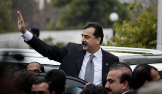 Pakistani Prime Minister Yousuf Raza Gilani waves upon his arrival at the Supreme Court in Islamabad, Pakistan, on Monday, Feb. 13, 2012. The court charged Mr. Gilani with contempt for defying its orders to reopen an old corruption case against his political ally, President Asif Ali Zardari. (AP Photo/B.K. Bangash)