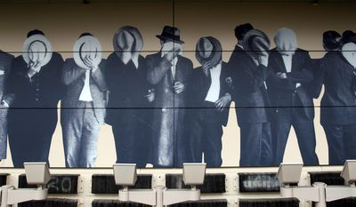 A photo of members of Detroit's Purple Gang hiding their faces in May 1929, when they were arrested on charges of providing protection to drug dealers, is displayed at the Mob Museum in Las Vegas. The publicly funded, $42 million museum, which opened Tuesday, makes the most of Las Vegas' deep mobster roots. (Associated Press)