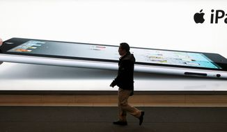 A man walks past an iPad2 advertisement in Shanghai on Monday. A Chinese company will ask customs officials to ban imports and exports of Apple Inc.'s iPads. (Associated Press)