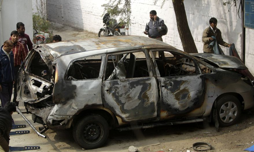 Police officers stand around an Israeli diplomat's car that was damaged in an explosion in New Delhi, India, Tuesday, Feb. 14, 2012. Indian investigators were searching Tuesday for the motorcycle assailant who attached a bomb to an Israeli diplomatic car in the heart of New Delhi in an attack the Jewish state blamed on Iran or its proxies. (AP Photo/Mustafa Quraishi)