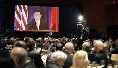 """Chinese Vice President Xi Jinping can be seen on a video screen as he speaks Wednesday to the U.S.-China Business Council in Washington. """"Despite some twists and turns, U.S.-China relations have continued moving forward,"""" he said. """"It is on a course that cannot be stopped or reversed."""" (Associated Press)"""