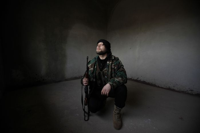 A Syrian rebel looks out after government tanks enter the northwestern city of Idlib, Syria, on Tuesday, Feb.